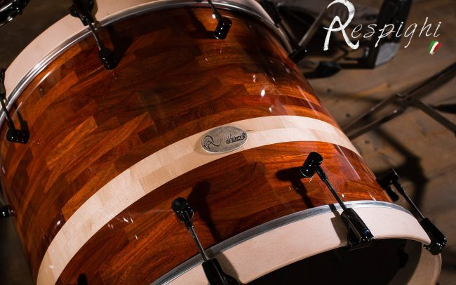 Detail of a Respighi Drums handmade bass drum in padouk and maple with black hardware